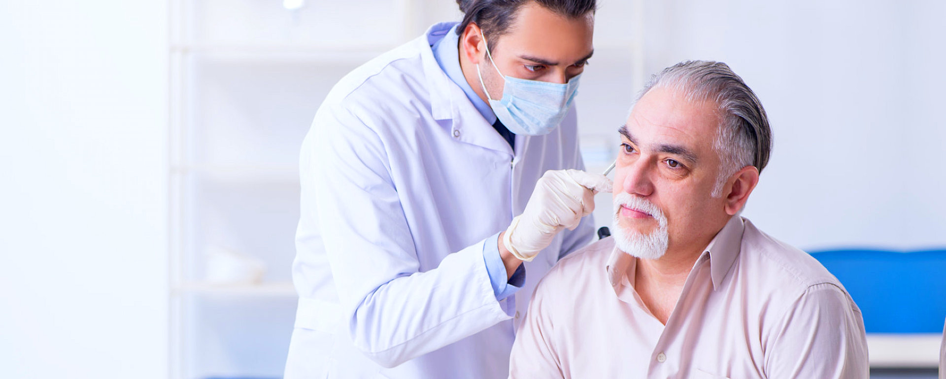 male physician checking pateint's hearing
